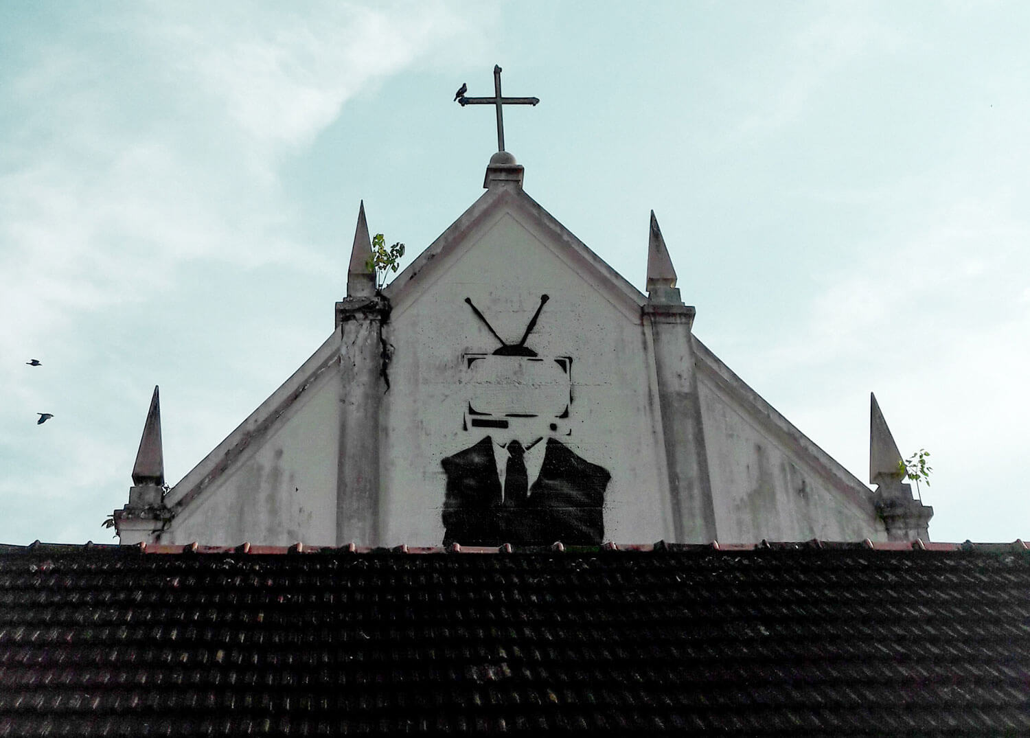 A photo illustration of a conspiracy-looking image graffitied onto the side of a church building.