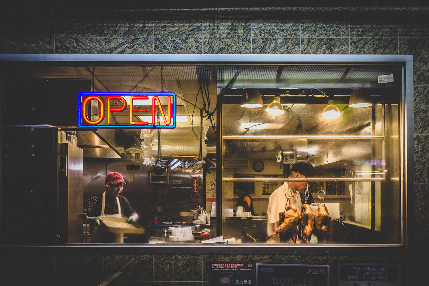 Two people standing in the kitchen of a restaurant in Chinatown, New York. Two roasted ducks and a glowing neon Open sign hang in the window.