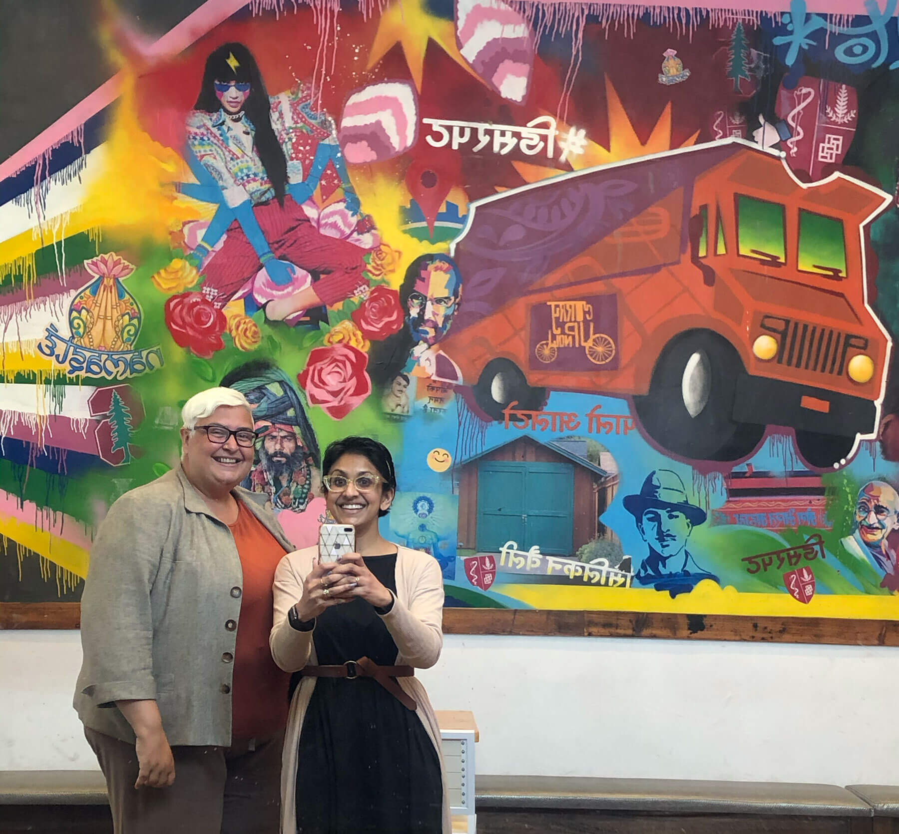 Sandhya Jha and Tuhina Verma Rasche take a selfie in front of a mural at Curry Up Now