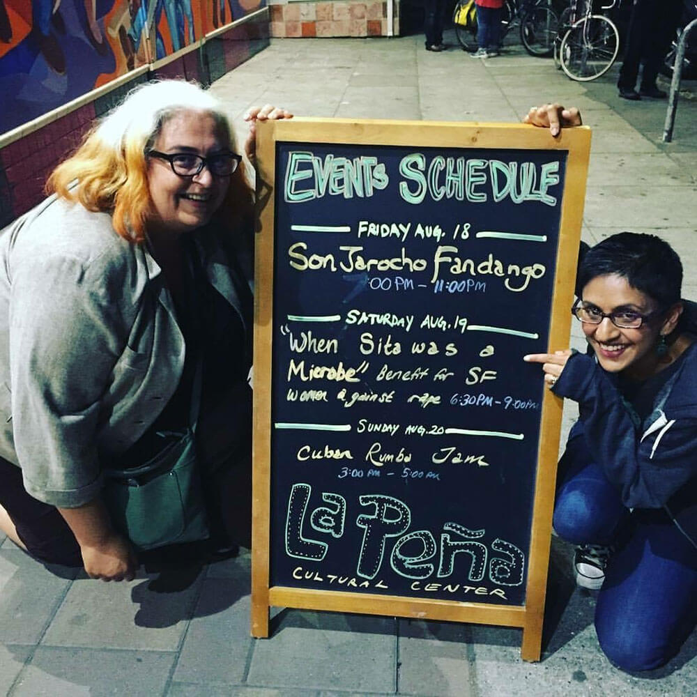 Sandhya Jha and Tuhina Verma Rasche together in front of a sign at La Peña Cultural Center