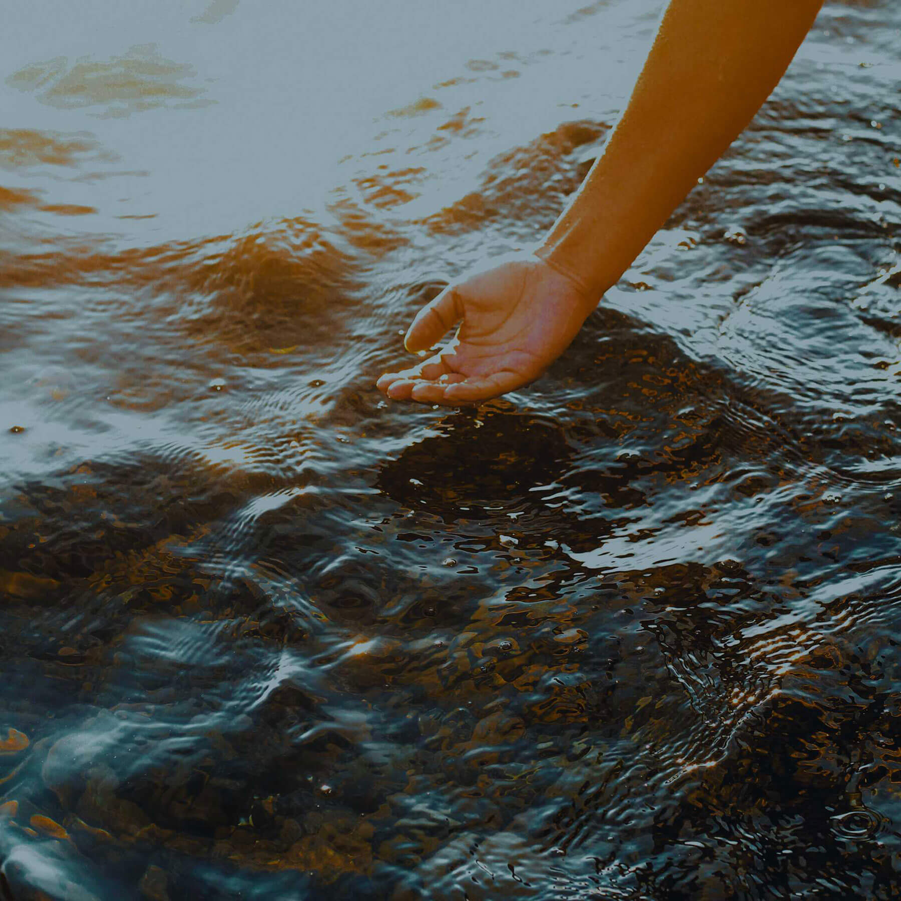 The back of a hand caresses a stream of moving water.
