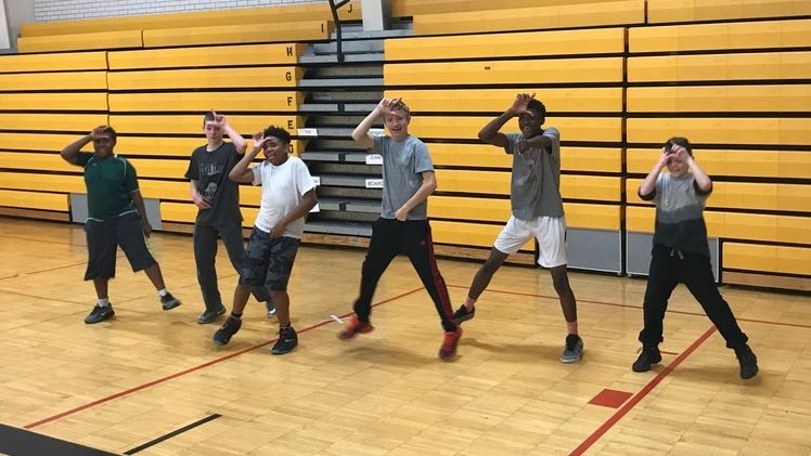 "Students in a gymnasium doing a dance from the video game ""Fortnite"""