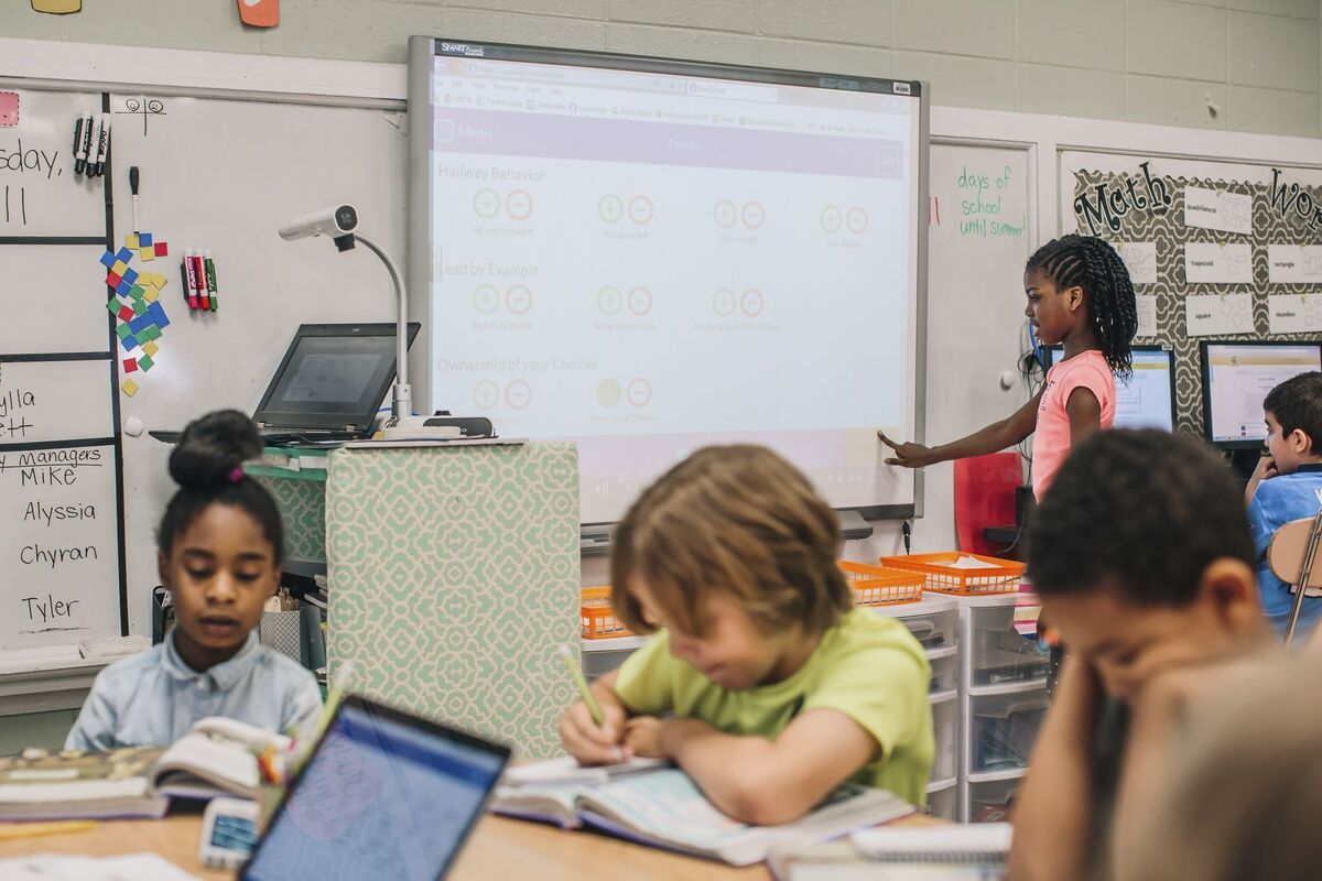 Students work at a table in the foreground, while a student is shown choosing a point from the behavior rubric on a smartboard in the background