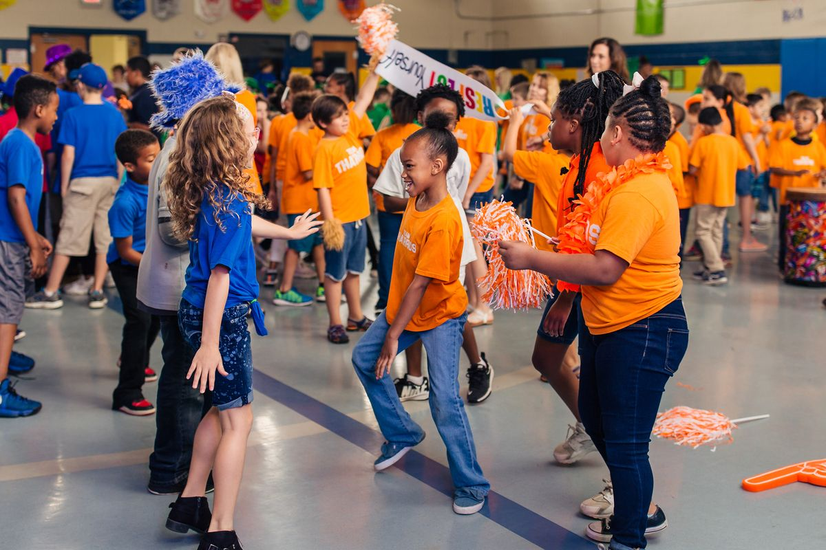 Students dancing in a circle at a House party, with half of the students shown wearing an orange House shirt, and the others wearing a blue House shirt