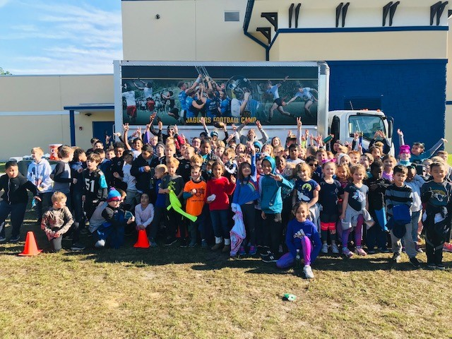 "A photo of students who won a PBIS raffle  in front of a truck with ""Jaguars Football Camp"" on the side"