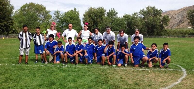 7 Faculty and 11 Students Pose on a Soccer Field during a Student/Faculty soccer game, with 2 student referees