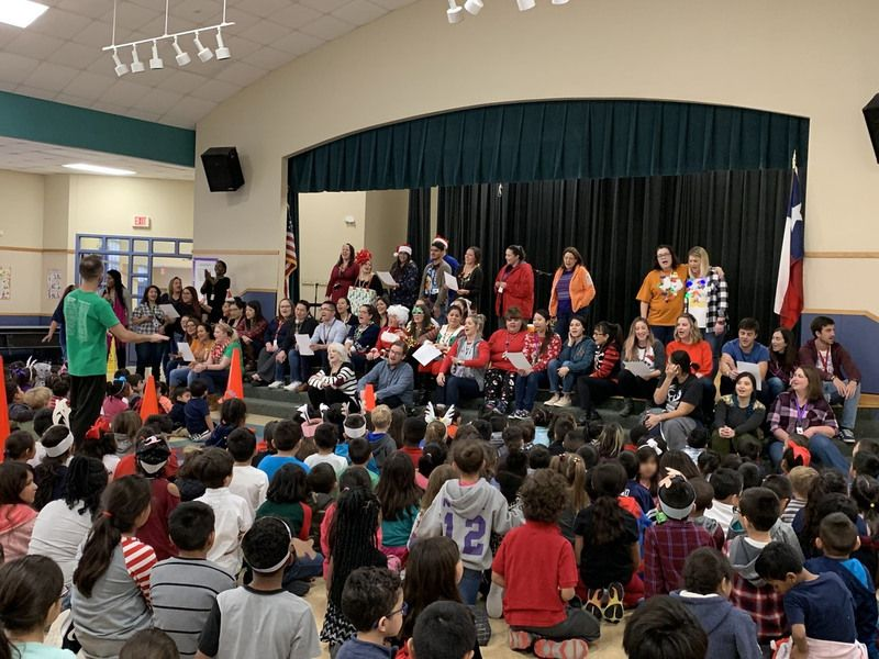 The school gathers at a holiday assembly, showing staff on stage singing and students singing along
