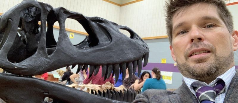 A school principal poses in front of a dinosaur exhibit