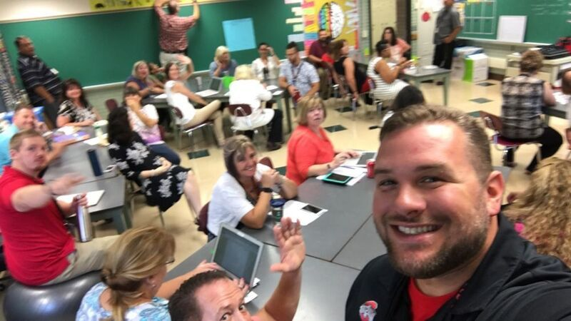 A teacher takes a selfie with other teachers at a faculty meeting