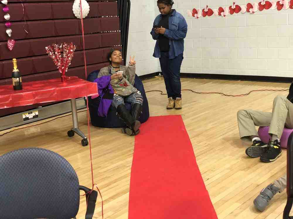 A student sits in a bean bag holding up a piece sign with a red carpet in front to show VIP section