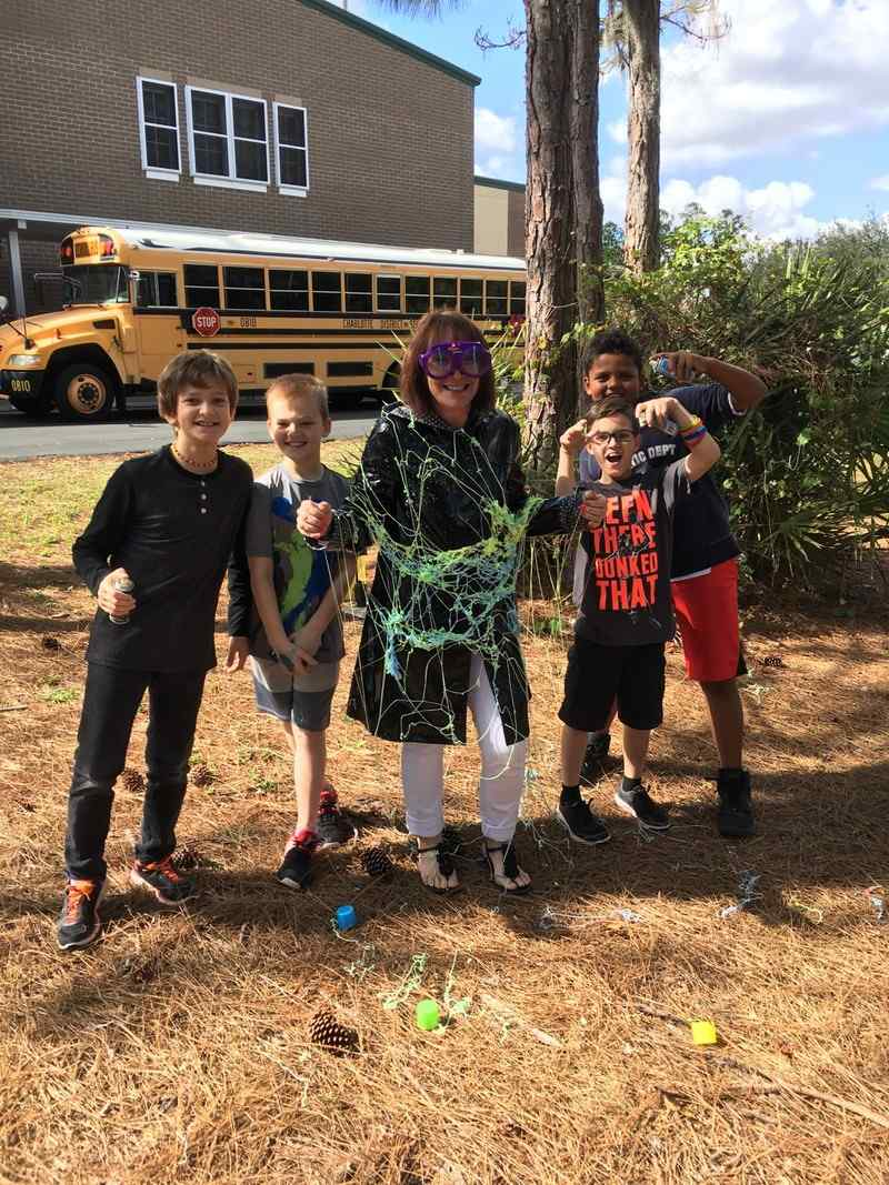A principal wearing safety goggles and covered in silly string stands next to students