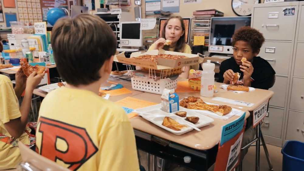 Students enjoying a pizza party at their desks in a classroom