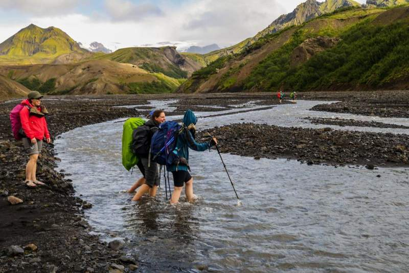backpackers-crossing-water-in-iceland