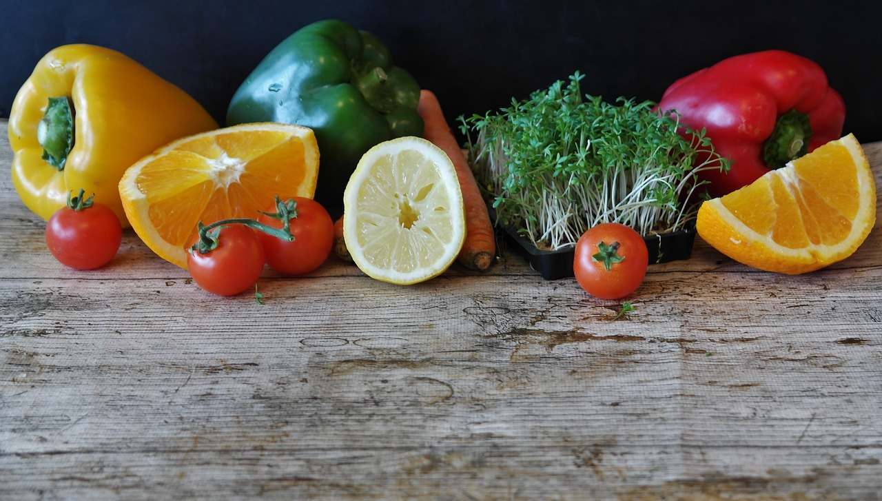 Vegetables and fruit including tomatoes, peppers, cress and fruit like oranges on a wooden board