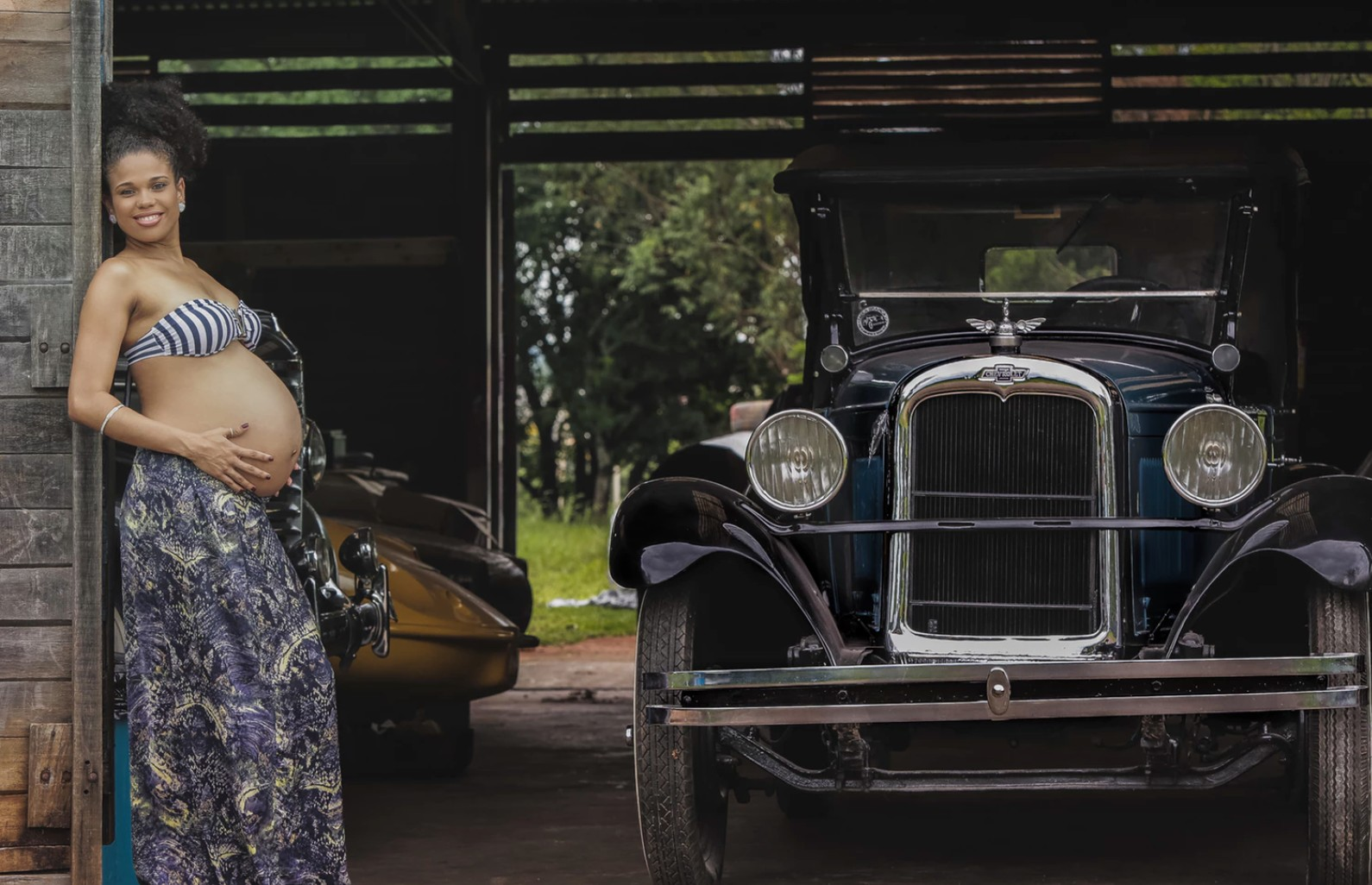 A pregnant woman poses by a classic car