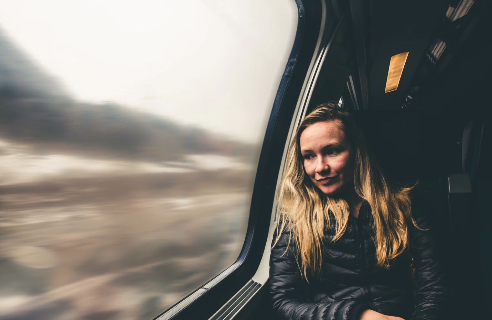 A young woman sits on the train