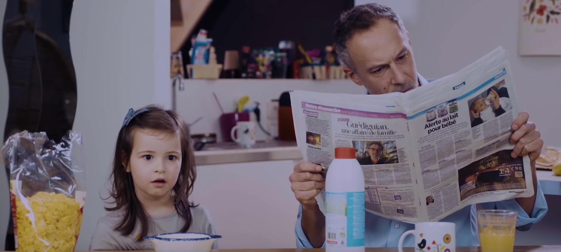 A little girl has breakfast with her father