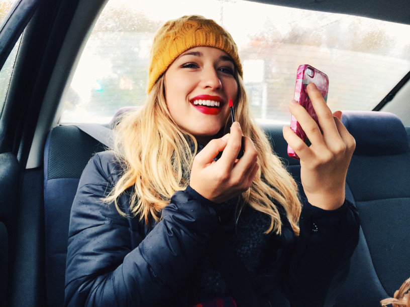 A young blonde woman applies lipstick