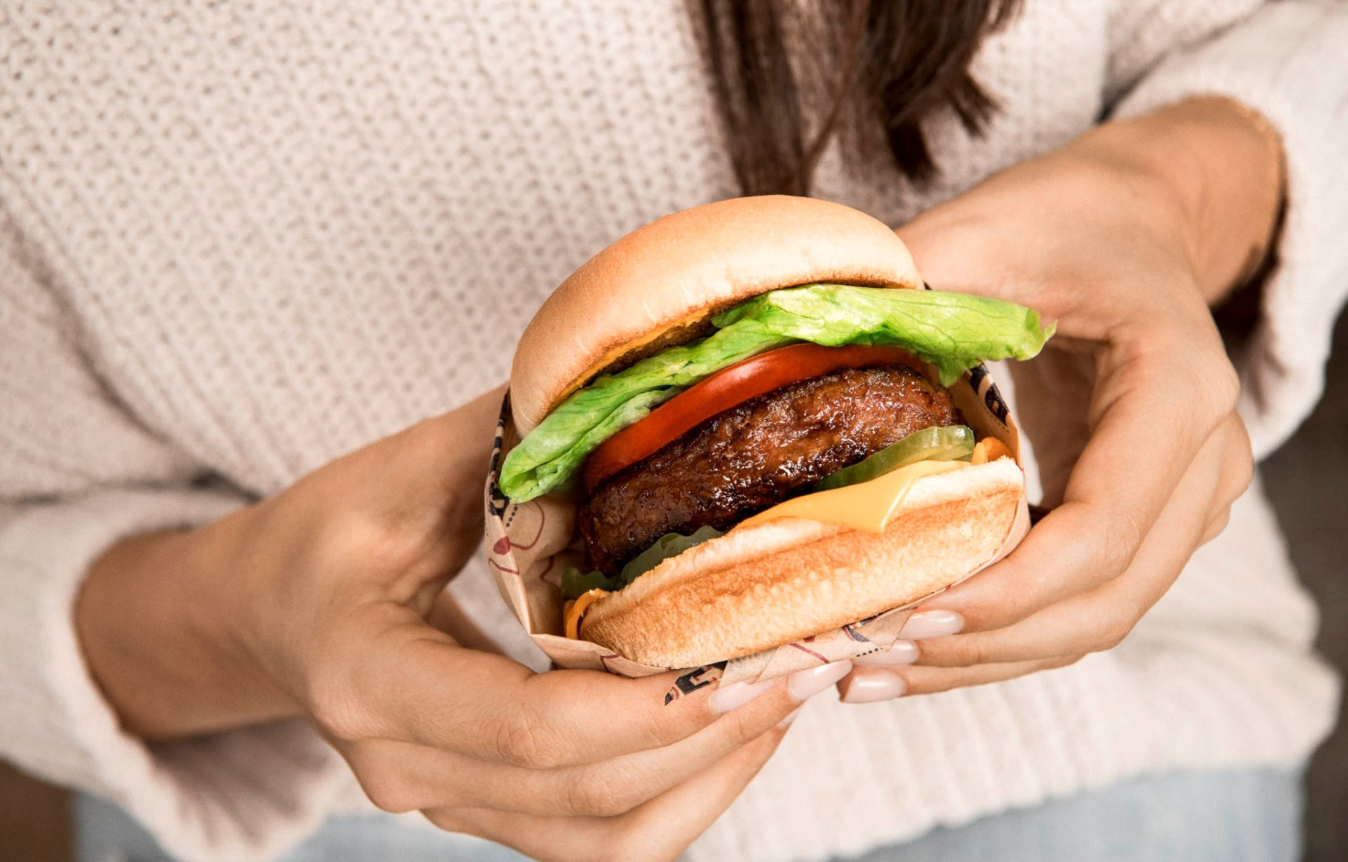 Woman holds vegan Beyond Burger from Beyond Meat