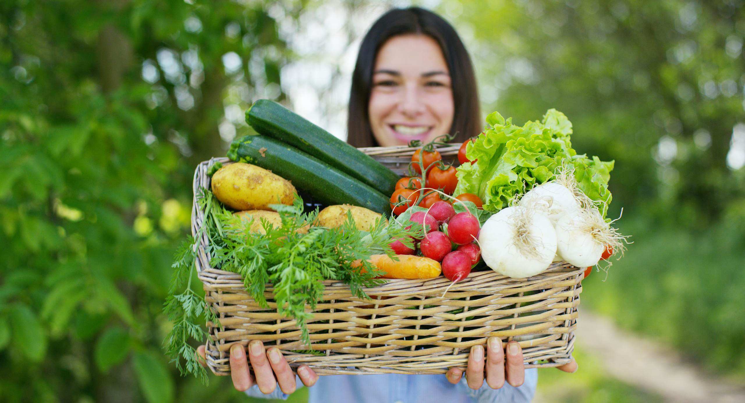 Woman holds basket of vegetables