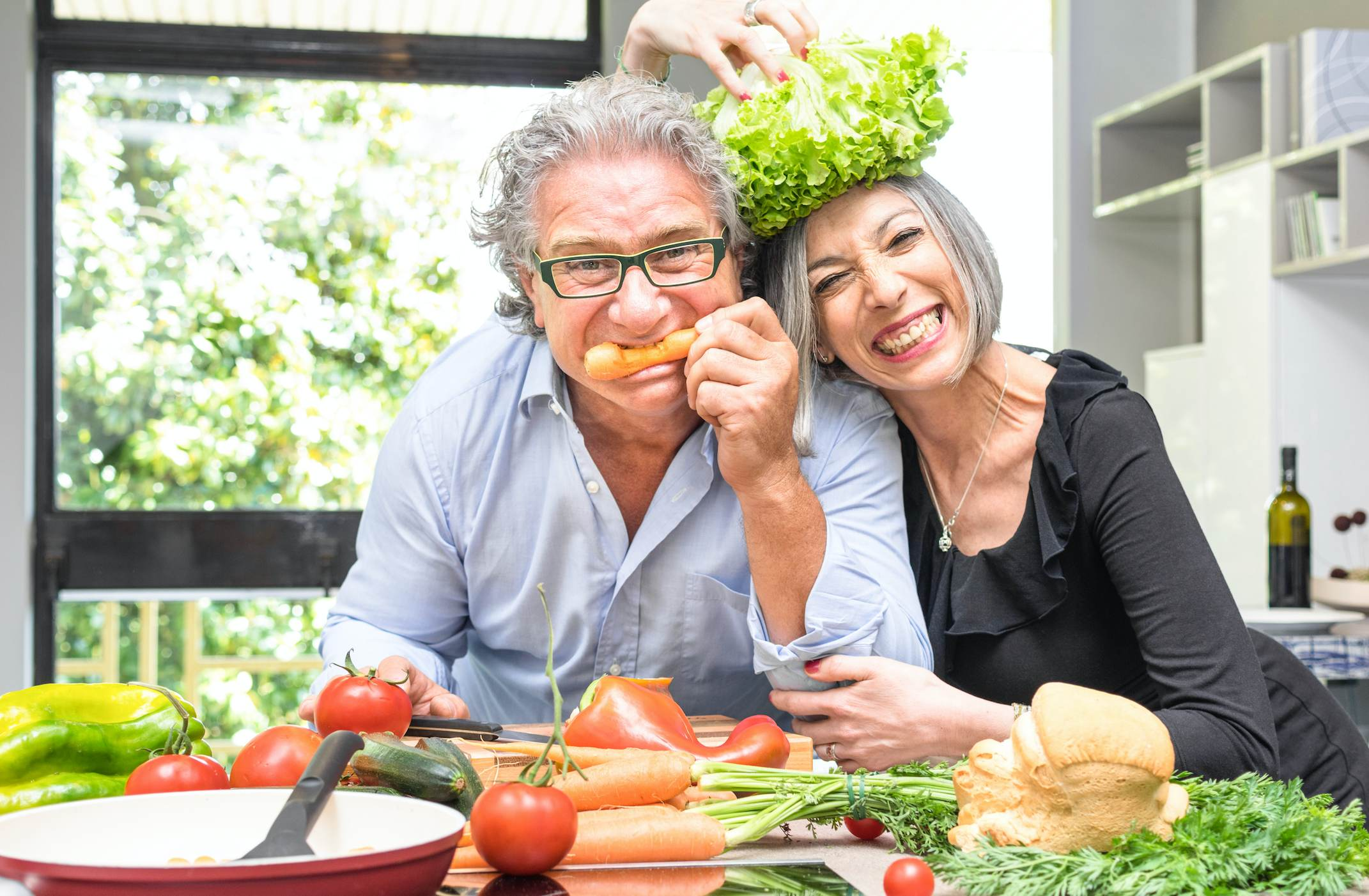 An old couple playing with vegetables