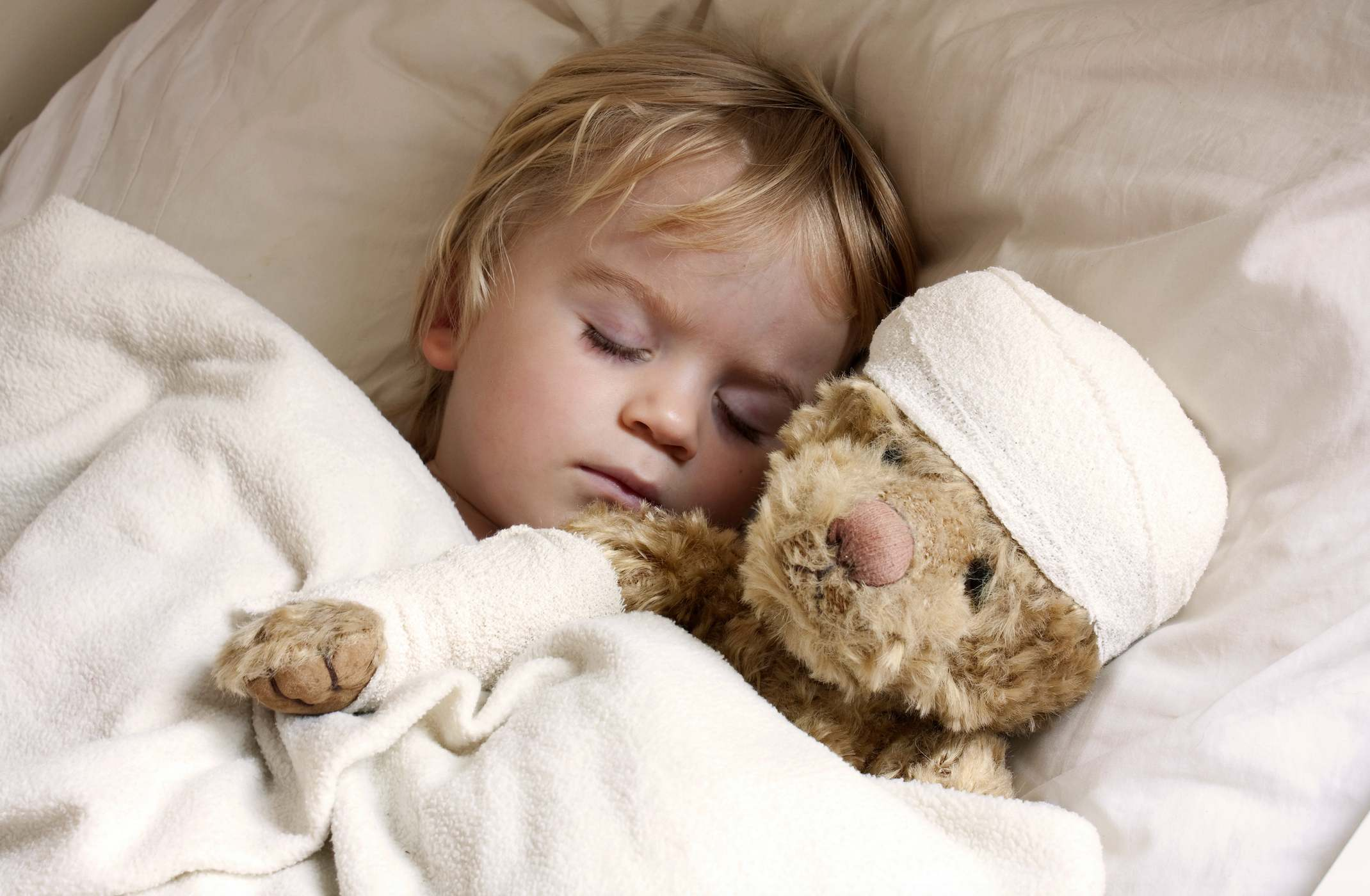Child in bed with teddybear