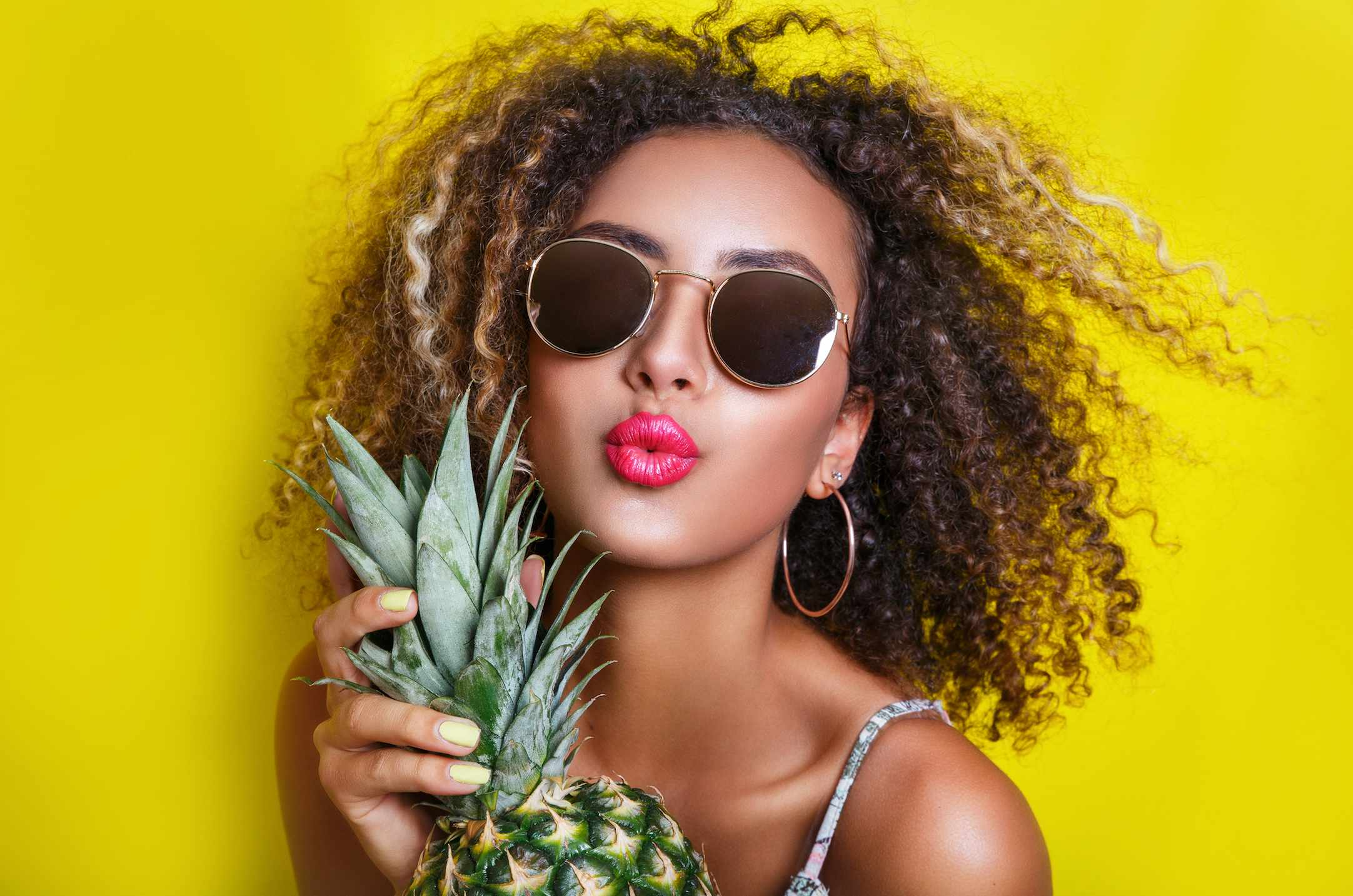 Woman wearing sunglasses holding a pineapple