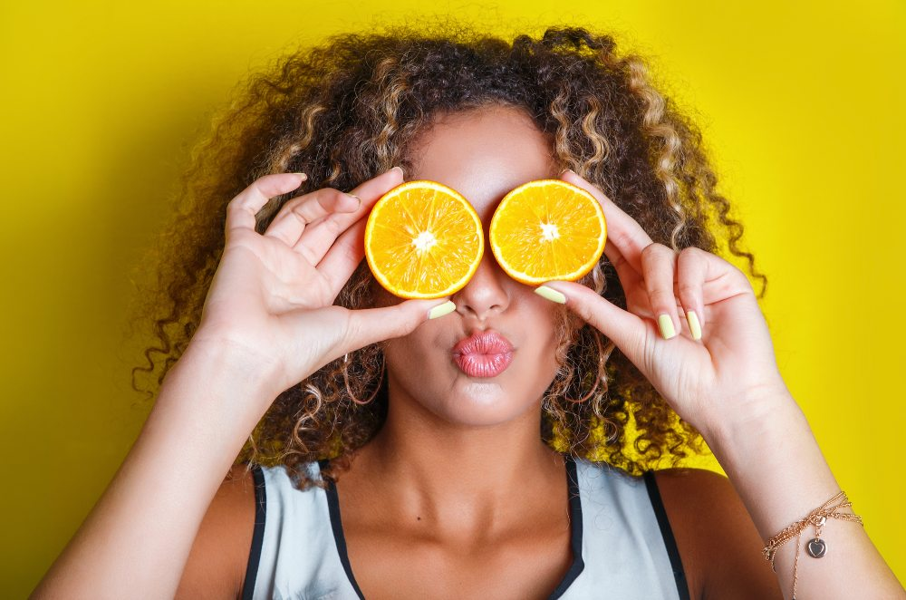 Woman holds oranges in front of her eyes