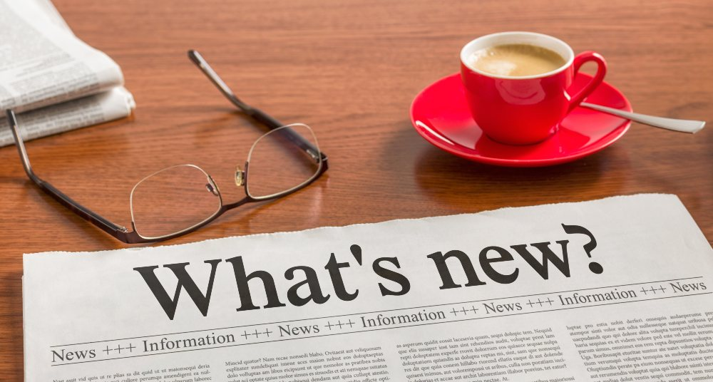 A newspaper, espresso, and pair of glasses