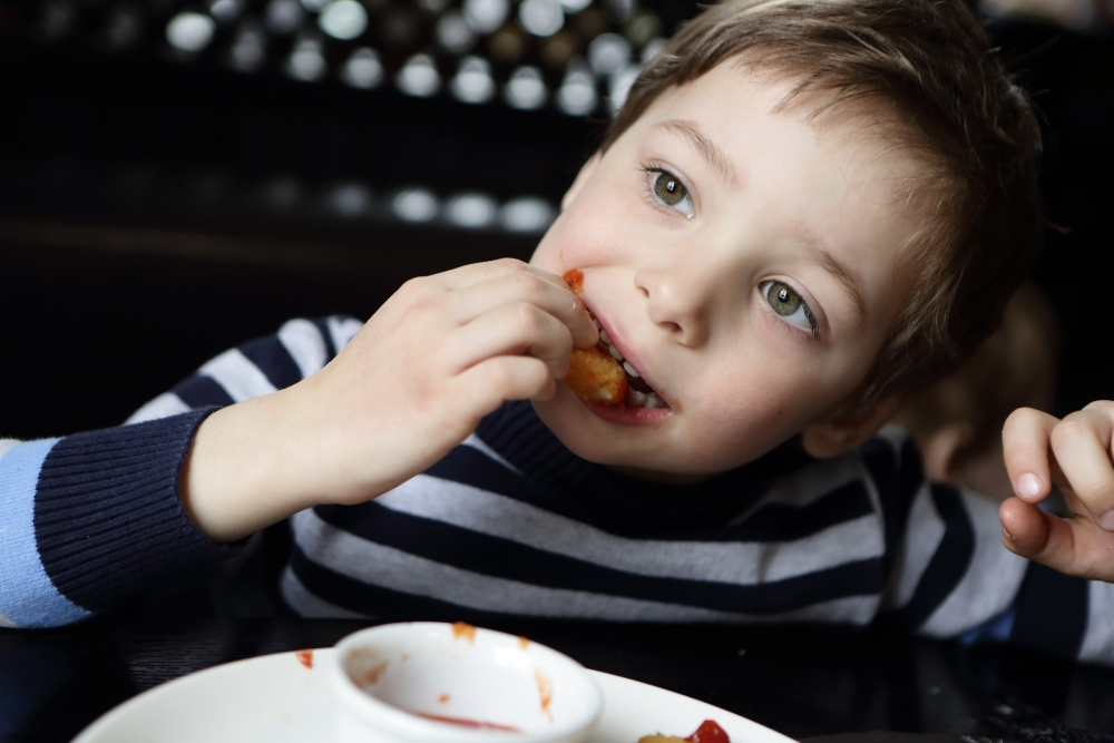 Little boy eating chicken nuggets