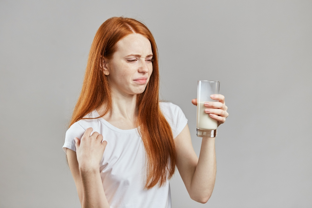 Woman looking disgsted at milk