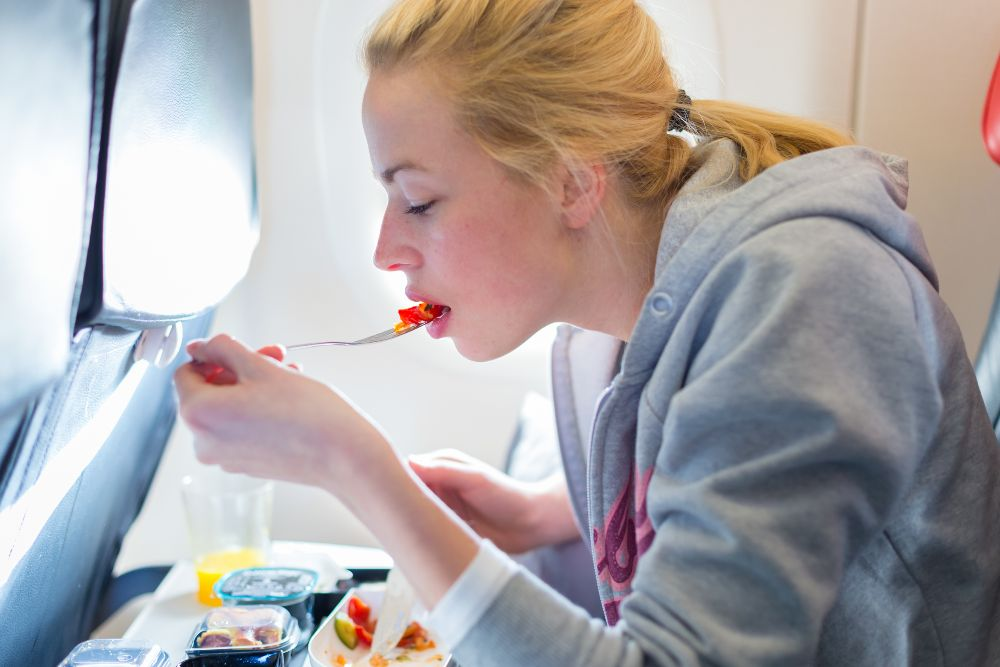 Woman eats meal on airplane