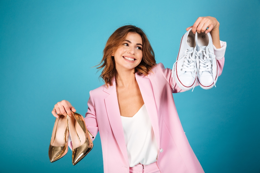 Woman holds two pairs of shoes