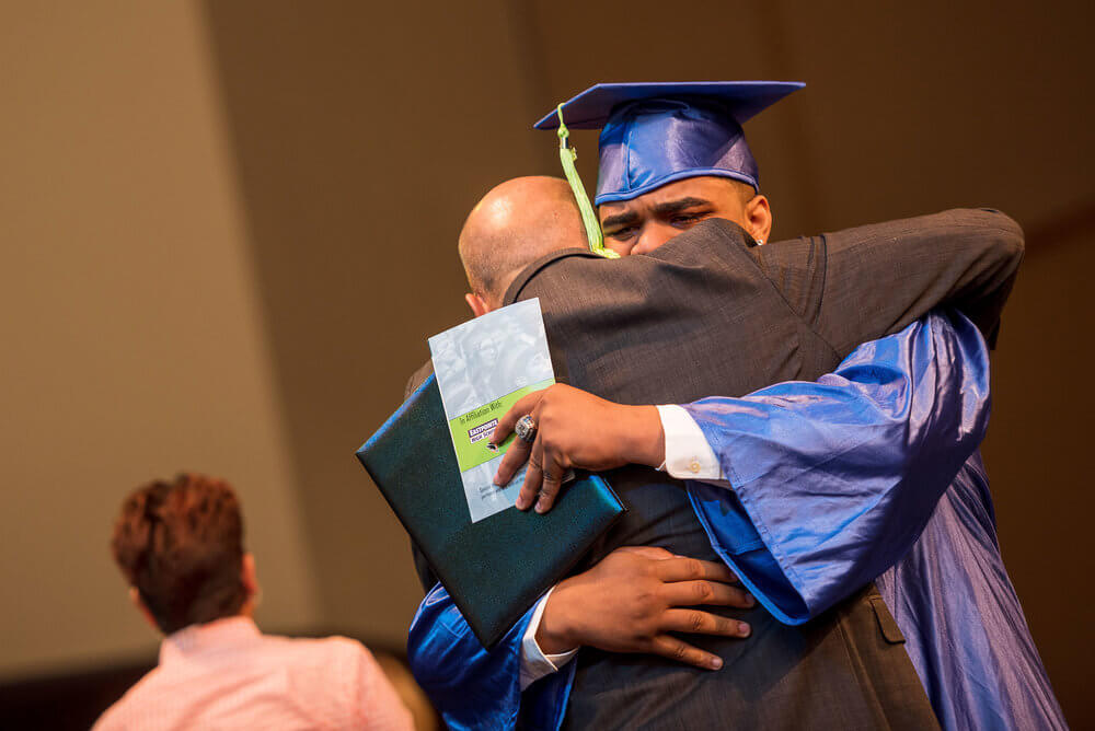 Graduation Solutions image of two people hugging as one gets presented his degree.