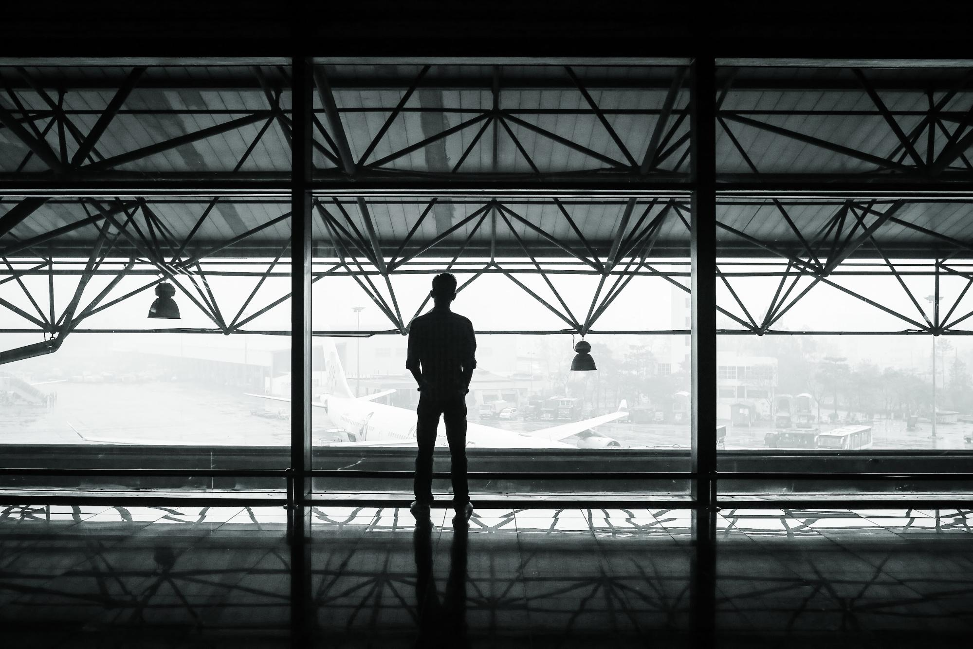 Man in terminal looking at airplane