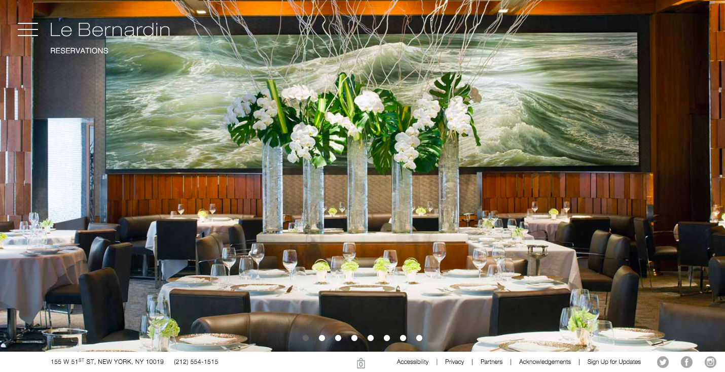 Le Bernardin homepage hero section. The inside of the empty restaurant with fancy table settings, linen cloths, and a flower display in front of a large ocean painting that covers most of the back wall.