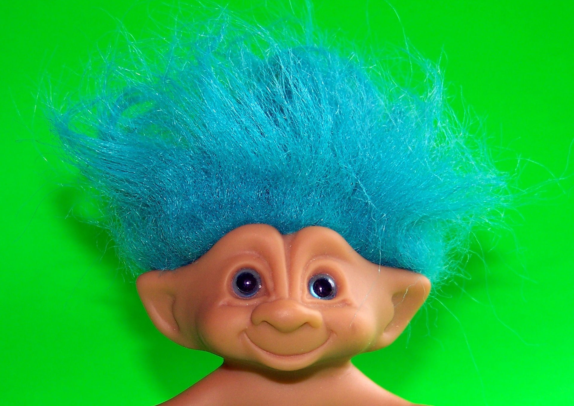 A closeup of a smiling, blue-haired troll head in front of a neon green background.