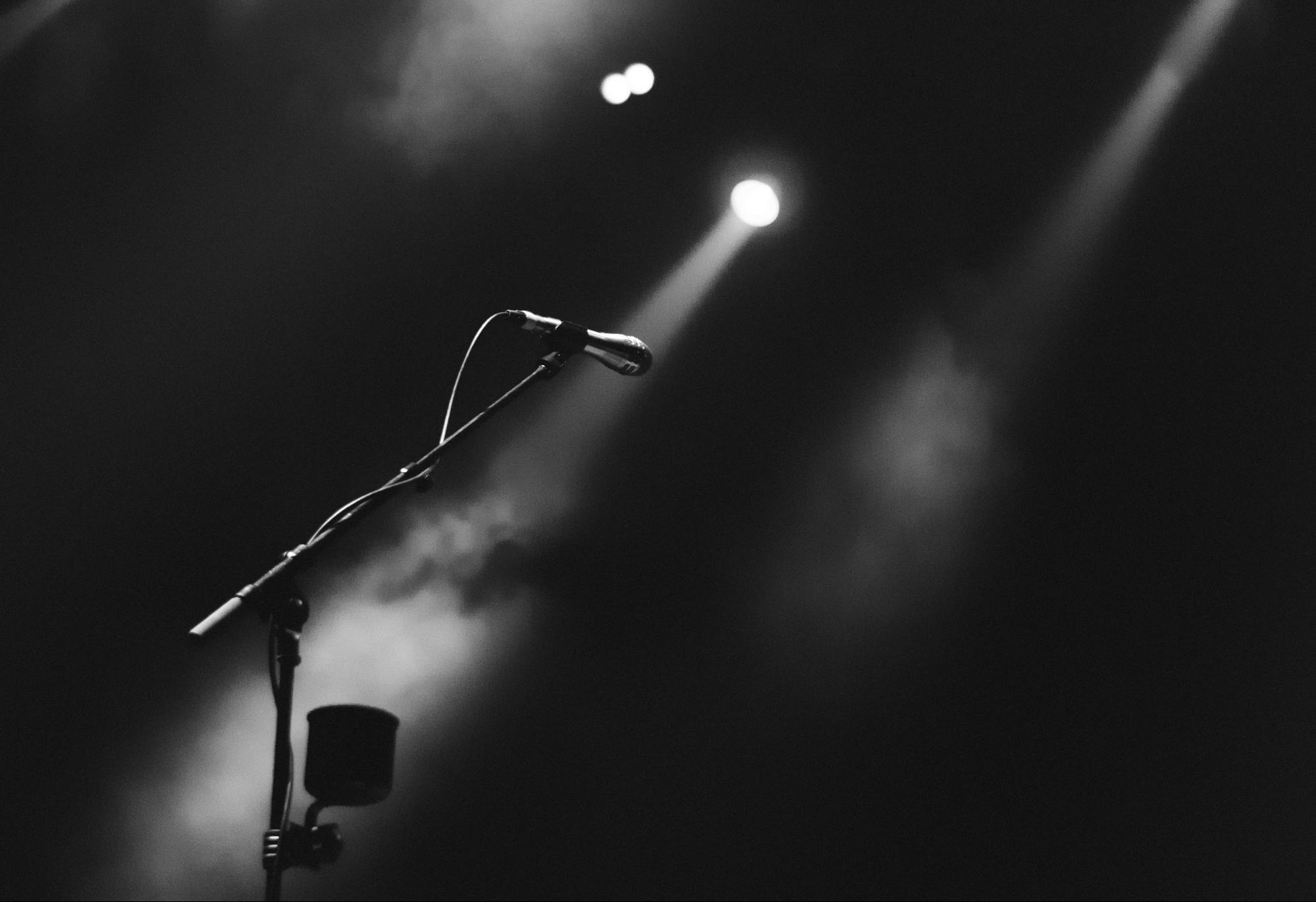 2 spotlight shining on a microphone in its stand on an empty stage.