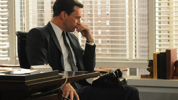 Don Draper in a thinking pose at his office desk.