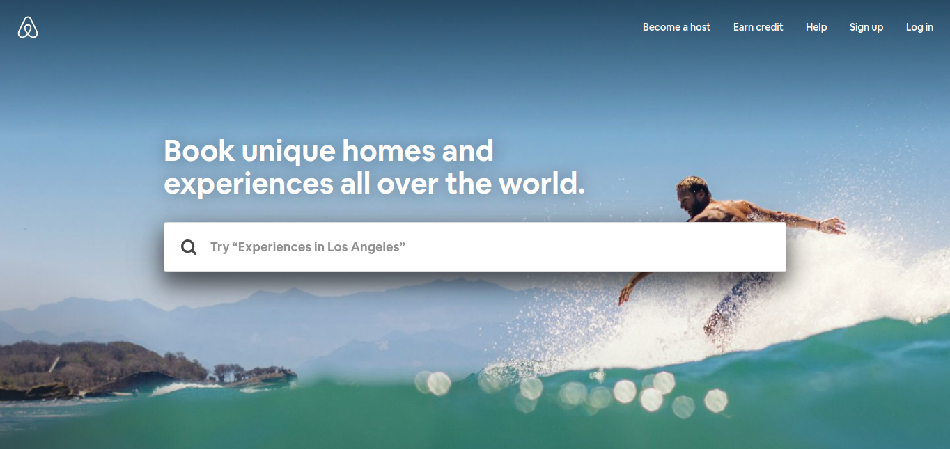 Hero image of a surfer in action with mountains in behind and the Airbnb search bar overlay