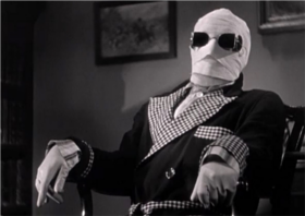 A screenshot of the main character from the movie Invisible Man. His face is wrapped in gauze and he's wearing sunglasses, sitting in a chair.