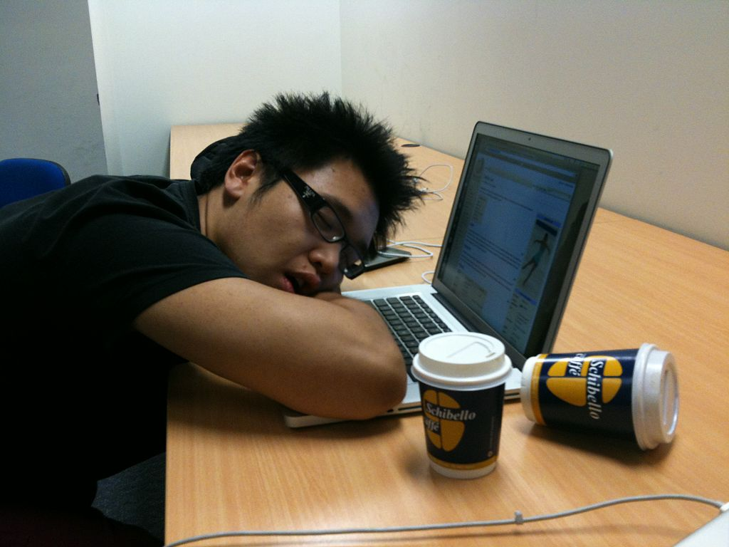 A person asleep at a desk with their head on their laptop. Two coffee cups sit on the desk beside them, one toppled over.