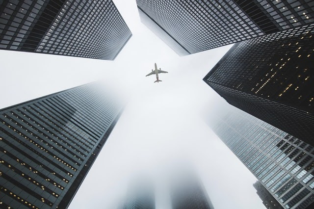 image of skyscrapers with airplane