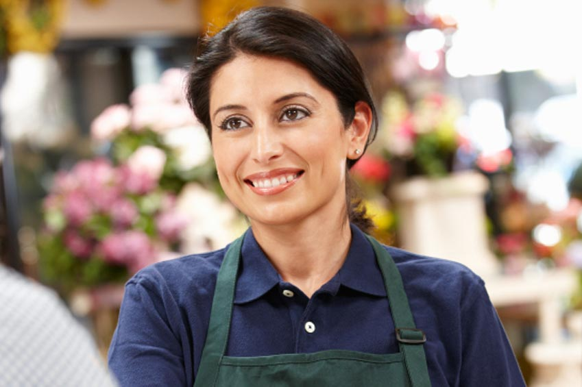 A smiling young woman in a blue shirt and green apron, stands in front of a blurred background of flowers in a shop.