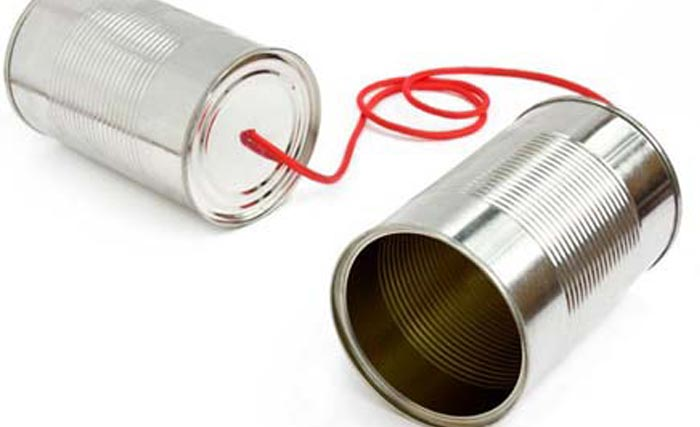 An old-school tin can phone; two tin cans lay on a white background, connected by a red string.