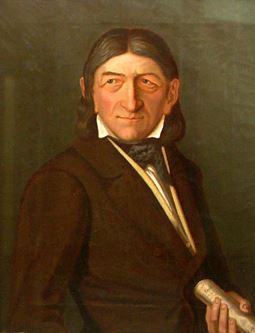 Portrait painting of Friedrich Fröbel; A man with shoulder-length brown hair in a dark brown suit jacket. His eyes are looking off to the left of the photo.