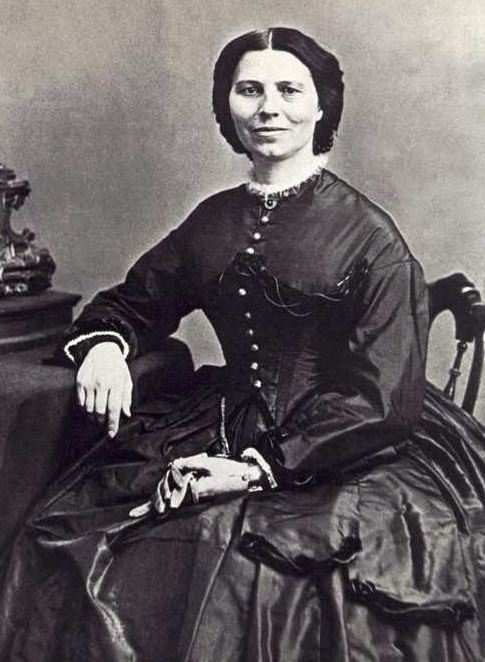 Portrait of Clara Barton; A woman in a late 19th century-style dress sits on a chair, her left arm resting on her lap and in her hands she holds a pair of gloves. Her right arm rests on the table directly beside her.