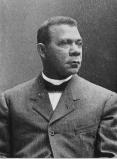 Portrait of Booker T. Washington; A sharply dressed man in a suit looks off to the right of the photograph, with an expression of deep thought.