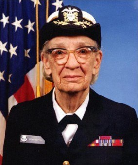 Portrait of Grace Hopper; an elderly woman wearing glasses and a naval uniform stands against an American flag.