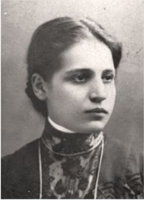 Portrait of Lise Meitner; a young woman looking stoically off to the right of the screen. She's wearing a high collared dress with her dark hair pulled back in what appears to be a low bun.